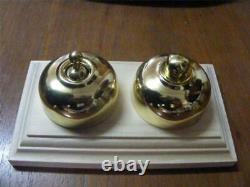 Polished brass light switch and dimmer on pine wooden block